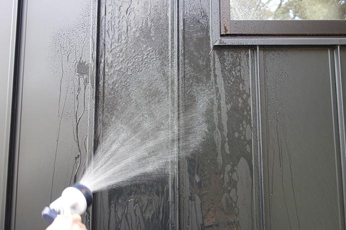 ゼロキューブ(ZERO-CUBE)のガルバリム鋼板の外壁を水で洗い流す写真