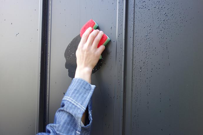 ゼロキューブ(ZERO-CUBE)のガルバリム鋼板の外壁を中性洗剤を含んだスポンジで洗っている様子