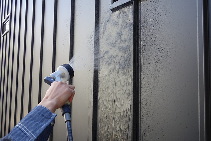 ゼロキューブ(ZERO-CUBE)のガルバリム鋼板の外壁を水で洗い流している様子